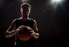 Profili la vista di una palla del canestro della tenuta del giocatore di pallacanestro su fondo nero fotografie stock