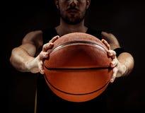 Profili la vista di una palla del canestro della tenuta del giocatore di pallacanestro su fondo nero Fotografie Stock Libere da Diritti