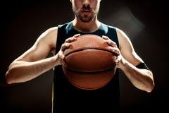Profili la vista di una palla del canestro della tenuta del giocatore di pallacanestro su fondo nero Immagini Stock