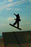 Profili lo snowboarder che salta su nel cielo blu Immagine Stock Libera da Diritti