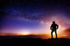 Profili una persona sta stando sulle montagne con la Via Lattea fotografie stock