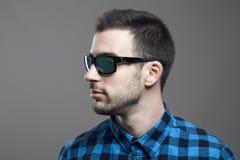 Profilieren Sie Ansicht des jungen bärtigen Mannes in der tragenden Sonnenbrille des karierten Hemds, die weg schaut Stockbilder