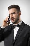 Profilieren Sie Ansicht des verärgerten wohlhabenden Mannes des Umkippens am Telefon, das weg schaut Stockbilder