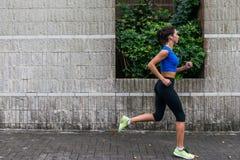 Profilieren Sie Ansicht einer sportlichen jungen Frau, die draußen ausarbeitet Eignungsmädchen, das auf Bürgersteig läuft lizenzfreie stockbilder