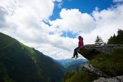 Profilieren Sie das Mädchen, das auf dem Felsen sitzt und ihre Beine im Abgrund baumeln stockfoto