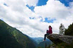 Profilieren Sie das Mädchen, das auf dem Felsen sitzt und ihre Beine im Abgrund baumeln stockfotos