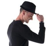 Profilieren Sie den Schuss des jungen Mannes lächelnd, rührenden Fedorahut Lizenzfreie Stockfotografie