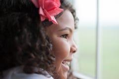 Glückliches Kind, das heraus Fenster schaut Stockfotografie