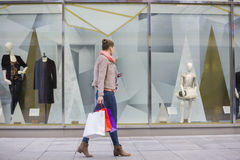 Profilieren Sie Schuss der jungen Frau mit den Einkaufstaschen, die Fensteranzeige betrachten stockfoto