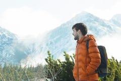 Profilo dell'alpinista sorridente che esamina incredibile vista nevosa delle sommità Fotografie Stock Libere da Diritti