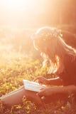 Profilo della ragazza in libro di lettura della corona, chiarore del sole Fotografie Stock