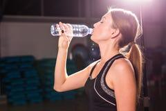Profilo di bella donna che va bere una certa acqua dalla bottiglia di plastica dopo l'allenamento fotografia stock libera da diritti