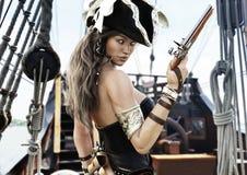 Profilo di un capitano femminile del pirata sexy che sta sulla piattaforma della sua nave con la pistola a disposizione illustrazione vettoriale