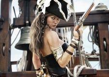 Profilo di un capitano femminile del pirata sexy che sta sulla piattaforma della sua nave con la pistola a disposizione illustrazione di stock