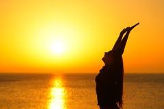 Profilo felice della donna che alza armi al tramonto sulla spiaggia immagini stock libere da diritti