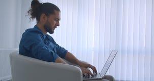 Profilo sparato delle free lance progressive che scrivono sul computer portatile che si siede in poltrona nell'comodo e leggero d archivi video