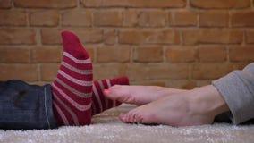 Profilo sparato delle gambe femminili e maschii che si trovano di fronte ad a vicenda e che abbracciano allegro su un tappeto sim video d archivio
