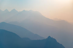 Profilo tonificato blu della siluetta e dell'abbazia della montagna al tramonto Fotografie Stock Libere da Diritti