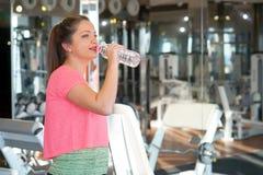 Profilowa młoda brunetki kobieta iść pić niektóre wodę od plastikowej butelki po treningu zdjęcie royalty free