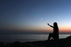 Profilowa sylwetka kobieta patrzeje na plaży przy zmierzchem Fotografia Stock