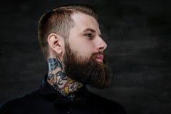 Profilowy portret ekspresyjny brodaty mężczyzna z tatuażami na jego szyi na ciemnym tle, obraz royalty free