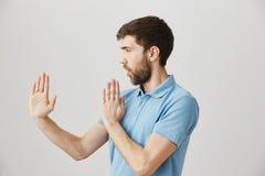 Profilowy portret figlarnie śliczny brodaty faceta mienie podnosił palmy w jak karate, stoi w obrończej pozie nad szarość Obraz Stock