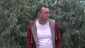 Profilowy portret mężczyzna z twarzą pełno pomadek oceny buziaki w parku, boczny widok na szczęśliwej twarzy zdjęcie wideo