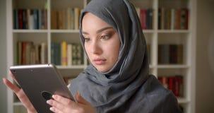 Profilowy portret muzu?ma?ski ucze? w hijab dopatrywaniu w pastylk? attentively jest zanurzony w pracowa? przy bibliotek? zdjęcie wideo