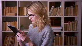 Profilowy portret w ?rednim wieku blondynka nauczyciel ogl?da attentively w pastylk? koncentruje przy bibliotek? zbiory