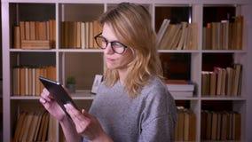 Profilowy portret w ?rednim wieku blondynka nauczyciel pracuje z pastylka zwrotami kamera i u?miechy przy bibliotek? zbiory