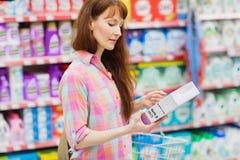 Profilowy widok kobieta z zakupy kosza mienia produktem fotografia stock