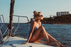 Profilporträt der jungen Frau sitzt auf der Plattform des Bootes lizenzfreie stockbilder