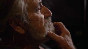 Profilporträt des müden älteren Mannes reibt seine Augen an der Dunkelkammer stock video footage