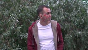 Profilporträt des Mannes mit Gesicht voll von Lippenstiftkennzeichen von Küssen im Park, Seitenansicht über glückliches Gesicht stock video footage