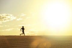 Profilschattenbild des jungen Mannes laufend in rüttelnde Disziplin des Landschaftstrainings-Cross Countrys im Sommersonnenunterg lizenzfreies stockfoto