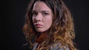 Profilsikt av den unga caucasian kvinnlign med lockigt brunt hår som vänder och ser kameran med en allvarlig ansiktsbehandling arkivfilmer