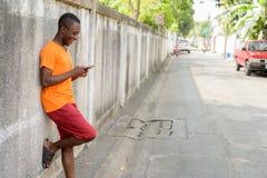 Profilsikt av den unga lyckliga svarta afrikanska mannen som smsar med telefonen arkivbild