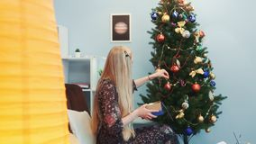 Profilsikt av hängande leksaker för trevlig dam på julgranen lager videofilmer
