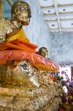 Profilsikt på en Buddhastaty som täckas med guld- sidor i Wat Chalong Buddhist Temple Royaltyfria Foton