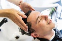 Profilsikten av en ung man som får hans hår tvättat och hans huvud, masserade i en hårsalong arkivfoto