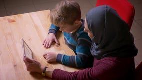 Profilskott av den lilla pojken och hans muslim moder i hållande ögonen på tecknade filmer för hijab på minnestavlan arkivfilmer
