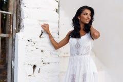 Profilståenden av en brud i en vit bröllopsklänning som lätt trycker på hennes hår, poserar nära en vit vägg som bort ser royaltyfria foton