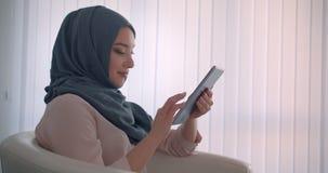 Profilu strzał muzułmański bizneswoman w hijab pracuje z pastylką ono uśmiecha się kamera jest radosny w biurze zdjęcie wideo