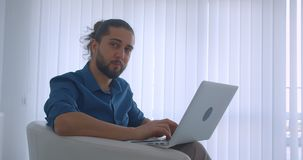 Profilu strzał pisać na maszynie na laptopu obsiadaniu w karle w lekkich biuro zwrotach kamera i uśmiechy nowożytny freelancer zdjęcie wideo