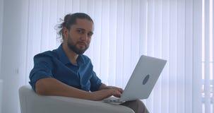 Profilu strzał pisać na maszynie na laptopu obsiadaniu w karle w lekkich biuro zwrotach kamera i zegarki nowożytny freelancer zbiory