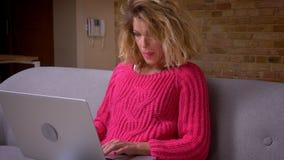 Profiluje strzał gospodyni domowa w różowym pulowerze pracuje attentively z laptopem jest baczny w domowej atmosferze zdjęcie wideo