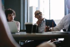 Profissionais incorporados durante a reunião da estratégia Imagens de Stock