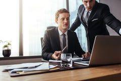 Profissionais incorporados que trabalham junto no portátil Imagem de Stock Royalty Free