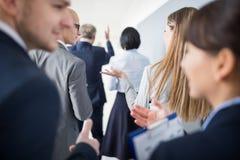 Profissionais que discutem ao andar com Team In Office foto de stock