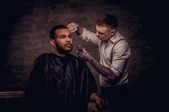 Profissional antiquado o cabeleireiro tattooed faz um corte de cabelo a um cliente afro-americano na obscuridade textured fotografia de stock royalty free